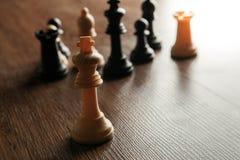 Κομμάτια σκακιού σε έναν ξύλινο πίνακα και ένα κομμάτι σκακιού του βασιλιά Στοκ Εικόνες