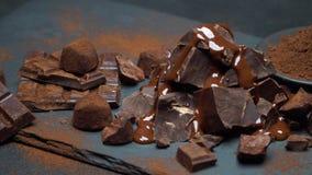 Κομμάτια σοκολάτας σκοταδιού ή γάλακτος, σιρόπι σοκολάτας και καραμέλες τρουφών στο σκοτεινό συγκεκριμένο υπόβαθρο απόθεμα βίντεο