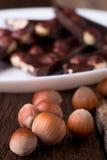 Κομμάτια σοκολάτας με τα καρύδια φουντουκιών στο άσπρο ξύλινο υπόβαθρο πιάτων κλείστε επάνω Στοκ φωτογραφία με δικαίωμα ελεύθερης χρήσης