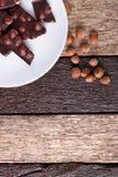Κομμάτια σοκολάτας με τα καρύδια φουντουκιών στο άσπρο ξύλινο υπόβαθρο πιάτων Τοπ όψη διάστημα αντιγράφων Πλαίσιο Στοκ Εικόνες