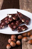 Κομμάτια σοκολάτας με τα καρύδια φουντουκιών στο άσπρο ξύλινο υπόβαθρο πιάτων κλείστε επάνω Στοκ Φωτογραφία
