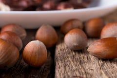 Κομμάτια σοκολάτας με τα καρύδια φουντουκιών στο άσπρο ξύλινο υπόβαθρο πιάτων κλείστε επάνω Στοκ Φωτογραφίες