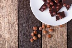 Κομμάτια σοκολάτας με τα καρύδια φουντουκιών στο άσπρο ξύλινο υπόβαθρο πιάτων Τοπ όψη διάστημα αντιγράφων Πλαίσιο Στοκ Φωτογραφία