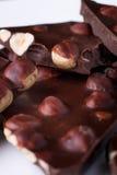 Κομμάτια σοκολάτας με τα καρύδια φουντουκιών στο άσπρο ξύλινο υπόβαθρο πιάτων κλείστε επάνω Στοκ Εικόνα