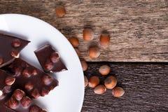 Κομμάτια σοκολάτας με τα καρύδια φουντουκιών στο άσπρο ξύλινο υπόβαθρο πιάτων διάστημα αντιγράφων Τοπ όψη Στοκ Εικόνες