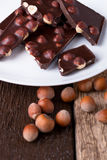 Κομμάτια σοκολάτας με τα καρύδια φουντουκιών στο άσπρο ξύλινο υπόβαθρο πιάτων Στοκ Εικόνες