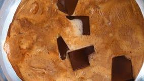 Κομμάτια σοκολάτας τήξης με το γάλα σε ένα κύπελλο, τοπ άποψη, βίντεο χρονικού σφάλματος απόθεμα βίντεο