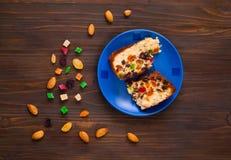 Κομμάτια σπιτικά muffins με τις σταφίδες, τα γλασαρισμένα φρούτα και τα αμύγδαλα σε ένα μπλε πιάτο σε ένα ξύλινο υπόβαθρο Στοκ φωτογραφία με δικαίωμα ελεύθερης χρήσης