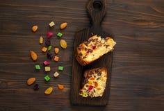 Κομμάτια σπιτικά muffins με τις σταφίδες, τα γλασαρισμένα φρούτα και τα αμύγδαλα σε ένα ξύλινο υπόβαθρο Υγιή συστατικά προγευμάτω Στοκ Φωτογραφία