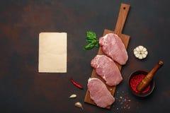 Κομμάτια της ακατέργαστης μπριζόλας χοιρινού κρέατος με το βασιλικό, το σκόρδο, το πιπέρι, το αλάτι και το κονίαμα και το κομμάτι στοκ εικόνες