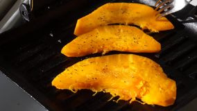 Κομμάτια της κολοκύθας που τηγανίζεται σε ένα τηγάνι σχαρών απόθεμα βίντεο