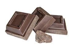 Κομμάτια της μαύρης σοκολάτας σε ένα άσπρο υπόβαθρο στοκ εικόνα με δικαίωμα ελεύθερης χρήσης