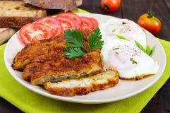 Κομμάτια της μπριζόλας schnitzel, φρυγανιά με τα αυγά, φρέσκια ντομάτα σε ένα σκοτεινό ξύλινο υπόβαθρο Στοκ Φωτογραφίες