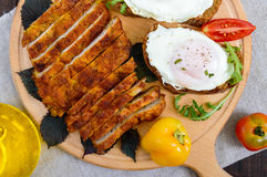 Κομμάτια της μπριζόλας schnitzel, φρυγανιά με τα αυγά, φρέσκια ντομάτα σε έναν ξύλινο πίνακα σε ένα σκοτεινό υπόβαθρο Στοκ φωτογραφίες με δικαίωμα ελεύθερης χρήσης