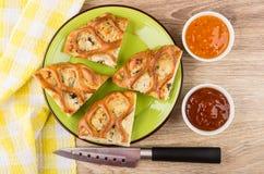 Κομμάτια της πίτας κοτόπουλου που γεμίζεται στο πράσινο πιάτο, μαχαίρι, σάλτσες Στοκ φωτογραφία με δικαίωμα ελεύθερης χρήσης