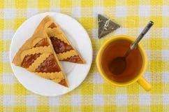 Κομμάτια της πίτας κουλουρακιών, του τσαγιού και του πακέτου τσαγιού στο τραπεζομάντιλο Στοκ Εικόνες