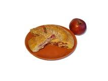 Κομμάτια της πίτας σμέουρων σε ένα πιάτο και ένα κόκκινο μήλο Στοκ Φωτογραφία