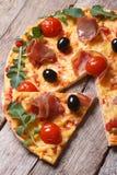 Κομμάτια της πίτσας με το prosciutto, το arugula και τις ντομάτες σε ξύλινο Στοκ Φωτογραφία