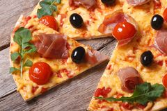 Κομμάτια της πίτσας με το prosciutto, arugula και κινηματογράφηση σε πρώτο πλάνο ντοματών Στοκ Φωτογραφία
