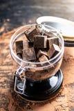 Κομμάτια της σκοτεινής πικρής σοκολάτας με το κακάο σε ένα βάζο γυαλιού στο ξύλινο υπόβαθρο Έννοια των συστατικών βιομηχανιών ζαχ στοκ εικόνες