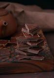Κομμάτια της σκοτεινής σοκολάτας σε έναν ξύλινο πίνακα στη μονοχρωματική ρύθμιση Στοκ Φωτογραφίες