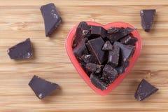 Κομμάτια της σκοτεινής σοκολάτας σε ένα κύπελλο καρδιών Στοκ Εικόνα