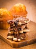 Κομμάτια της σοκολάτας και muffins σε ξύλινο στοκ εικόνες με δικαίωμα ελεύθερης χρήσης
