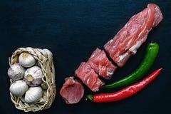 Κομμάτια της φρέσκιας λωρίδας χοιρινού κρέατος με το σκόρδο σε ένα ψάθινο καλάθι και των κόκκινων και πράσινων πιπεριών σε μια μα Στοκ φωτογραφία με δικαίωμα ελεύθερης χρήσης