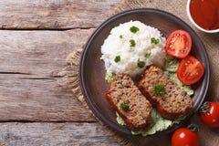 Κομμάτια της φραντζόλας κρέατος και του ρυζιού, λαχανικά σε μια τοπ άποψη πιάτων Στοκ Εικόνα