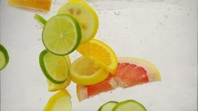 Κομμάτια του ασβέστη εσπεριδοειδών, λεμόνι, πορτοκάλι, πτώση γκρέιπφρουτ στο νερό με τους παφλασμούς και τις φυσαλίδες, σε αργή κ φιλμ μικρού μήκους