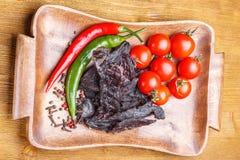 Κομμάτια του βόειου κρέατος jerky, των ντοματών, του καυτών πιπεριού και των καρυκευμάτων σε έναν ξύλινο δίσκο σε έναν ξύλινο πίν Στοκ Φωτογραφίες