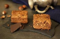 Κομμάτια του κέικ και της σοκολάτας στο πιάτο σχιστόλιθου, επόμενα φουντούκια Στοκ Εικόνες
