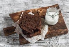 Κομμάτια του κέικ και του γιαουρτιού σοκολάτας σε έναν ξύλινο πίνακα Στοκ Εικόνες
