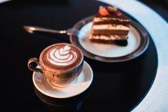 Κομμάτια του κέικ Καυτός καφές κακάου σοκολάτας ποτών στα φλυτζάνια Μαύρη ανασκόπηση Στοκ Εικόνα