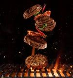Κομμάτια του κομματιασμένου γεύματος για τα χάμπουργκερ που πετούν επάνω από τη σχάρα Στοκ φωτογραφίες με δικαίωμα ελεύθερης χρήσης