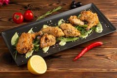 Κομμάτια του κοτόπουλου στο κτύπημα σε ένα μαύρο πιάτο σε ένα ξύλινο υπόβαθρο στοκ εικόνες