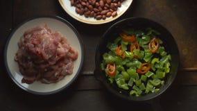 Κομμάτια του κοτόπουλου, φασόλια Πιπέρι και τσίλι κατά μια παν άποψη τηγανίσματος άνωθεν βίντεο απόθεμα βίντεο