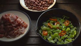 Κομμάτια του κοτόπουλου, φασόλια Πιπέρι και τσίλι σε μια τηγανίζοντας παν κινηματογράφηση σε πρώτο πλάνο βίντεο απόθεμα βίντεο