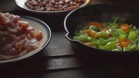 Κομμάτια του κοτόπουλου, φασόλια Πράσινα πιπέρι και τσίλι σε ένα τηγανίζοντας τηγάνι βίντεο φιλμ μικρού μήκους