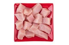 Κομμάτια του κρέατος κοτόπουλου στο πιάτο κόκκινων τετραγώνων στο λευκό Στοκ Εικόνα