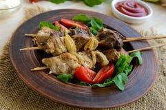 Κομμάτια του κρέατος με τα κρεμμύδια στα οβελίδια & x28 kebab& x29  Εξυπηρετήστε με τη σάλτσα, τις ντομάτες και το arugula Στοκ Εικόνα