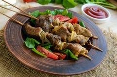 Κομμάτια του κρέατος με τα κρεμμύδια στα οβελίδια & x28 kebab& x29  Εξυπηρετήστε με τη σάλτσα, τις ντομάτες και το arugula Στοκ φωτογραφία με δικαίωμα ελεύθερης χρήσης