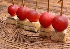 Κομμάτια του μπλε τυριού και των κόκκινων σταφυλιών Στοκ Εικόνες
