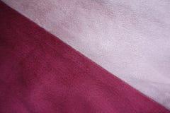 Κομμάτια του ρόδινου και κόκκινου τεχνητού σουέτ που συρράπτεται διαγώνια Στοκ φωτογραφία με δικαίωμα ελεύθερης χρήσης