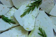 Κομμάτια του τυριού φέτας που βρέχεται με το ελαιόλαδο Ευώδη κλαδάκια του φρέσκου δεντρολιβάνου Στοκ Εικόνες