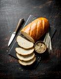 Κομμάτια του ψωμιού με ένα μαχαίρι, ένα σιτάρι και spikelets στοκ φωτογραφία
