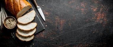 Κομμάτια του ψωμιού με ένα μαχαίρι, ένα σιτάρι και spikelets στοκ φωτογραφία με δικαίωμα ελεύθερης χρήσης