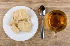 Κομμάτια του halva φυστικιών στο πιάτο, το τσάι και το κουταλάκι του γλυκού Στοκ φωτογραφία με δικαίωμα ελεύθερης χρήσης