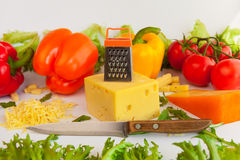 Κομμάτια των τυριών, του ξυμένου τυριού, της σχάρας μετάλλων, του μαχαιριού, των ντοματών, των πιπεριών και των φύλλων των frilli Στοκ Φωτογραφία