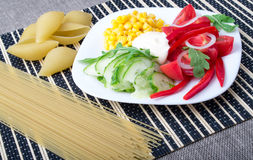 Κομμάτια των φρέσκων ακατέργαστων λαχανικών σε ένα άσπρο πιάτο Στοκ Εικόνα
